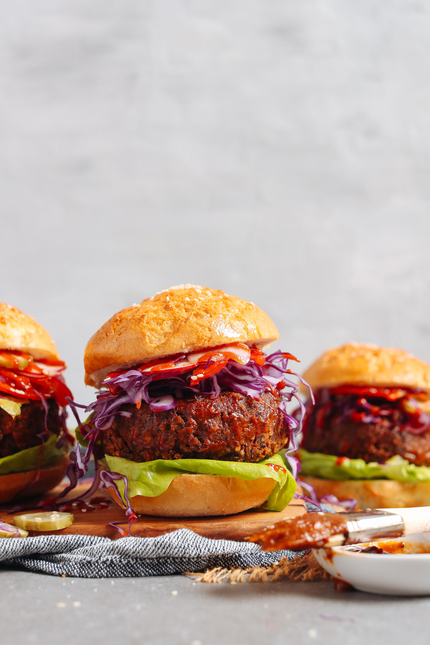 Three BBQ Black Bean Burgers served on buns with red bell pepper, cabbage, and lettuce
