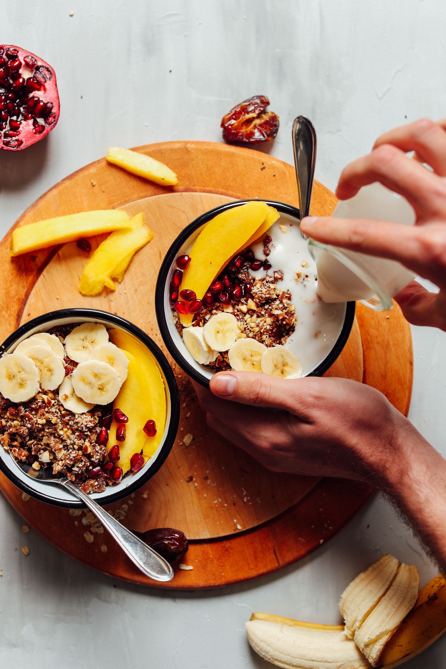 Pouring coconut milk into a bowl of gluten-free vegan granola with fresh fruit