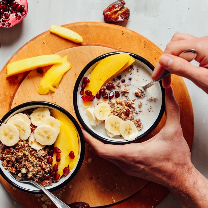 Wholesome bowls of gluten-free vegan granola served with coconut milk and fresh fruit