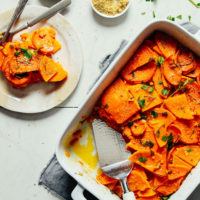 A small plate serving of Vegan Sweet Potato Butternut Squash Tortilla placed beside the freshly baked whole dish