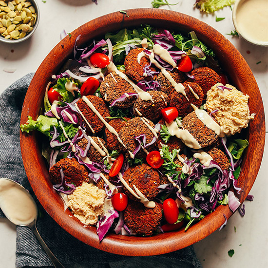 Large wood bowl with Baked Quinoa Black Bean Falafel over green salad