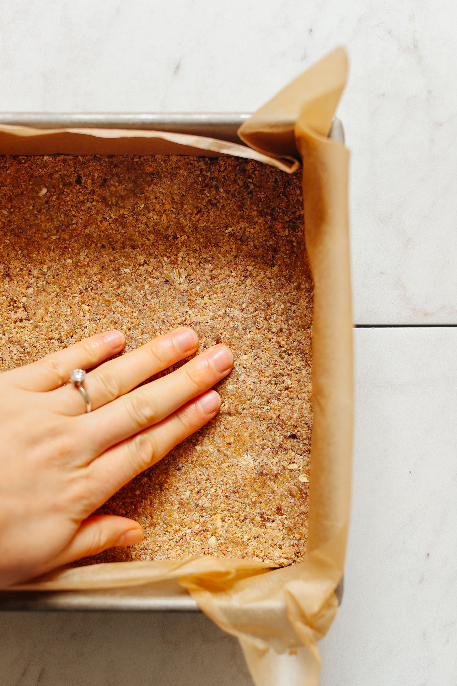 Parchment-lined metal baking pan with crust layer for these Vegan 7-Layer Bars