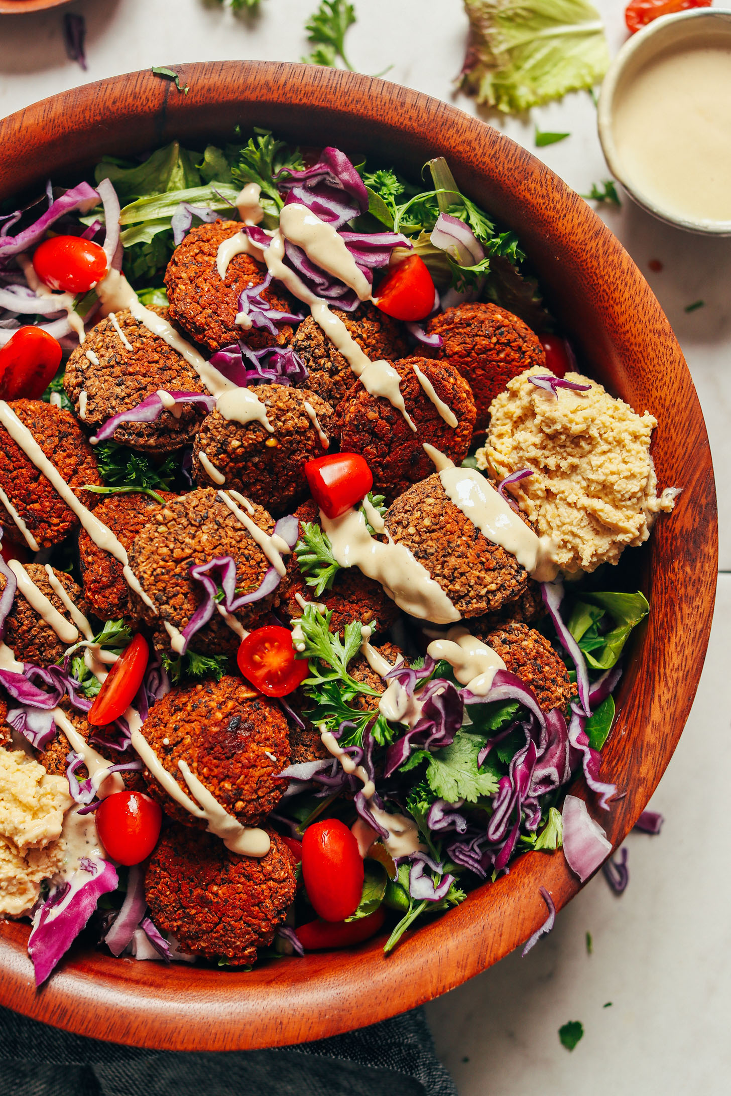 Serving bowl featuring our Black Bean Quinoa Falafel on a bed of mixed greens