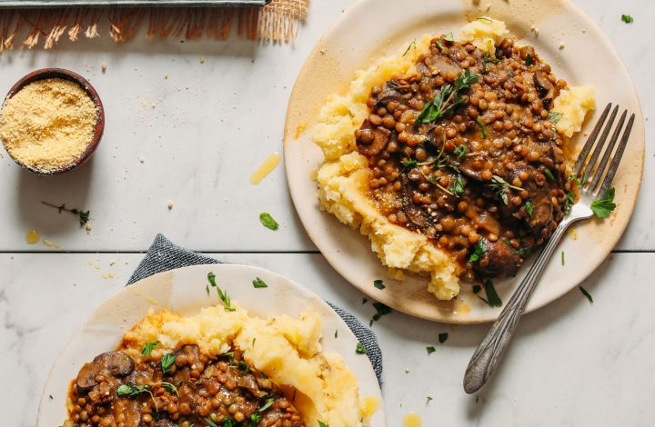 Plates of Lentil Mushroom Stew topped with fresh thyme served over mashed potatoes