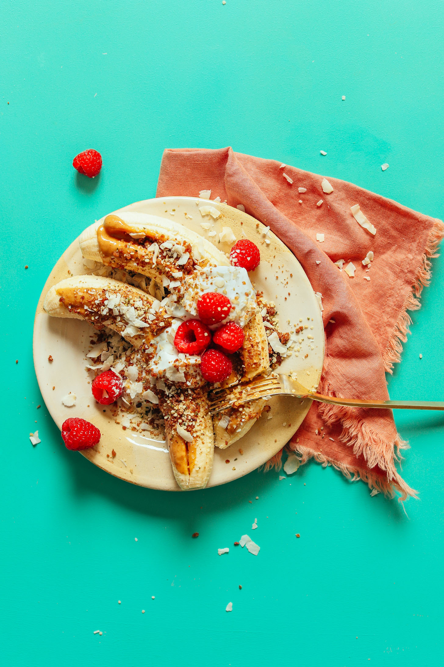 A serving plate with these protein and fiber-rich Raw Banana Splits served with Nut Butter, Coconut Yogurt, Berries, and more!