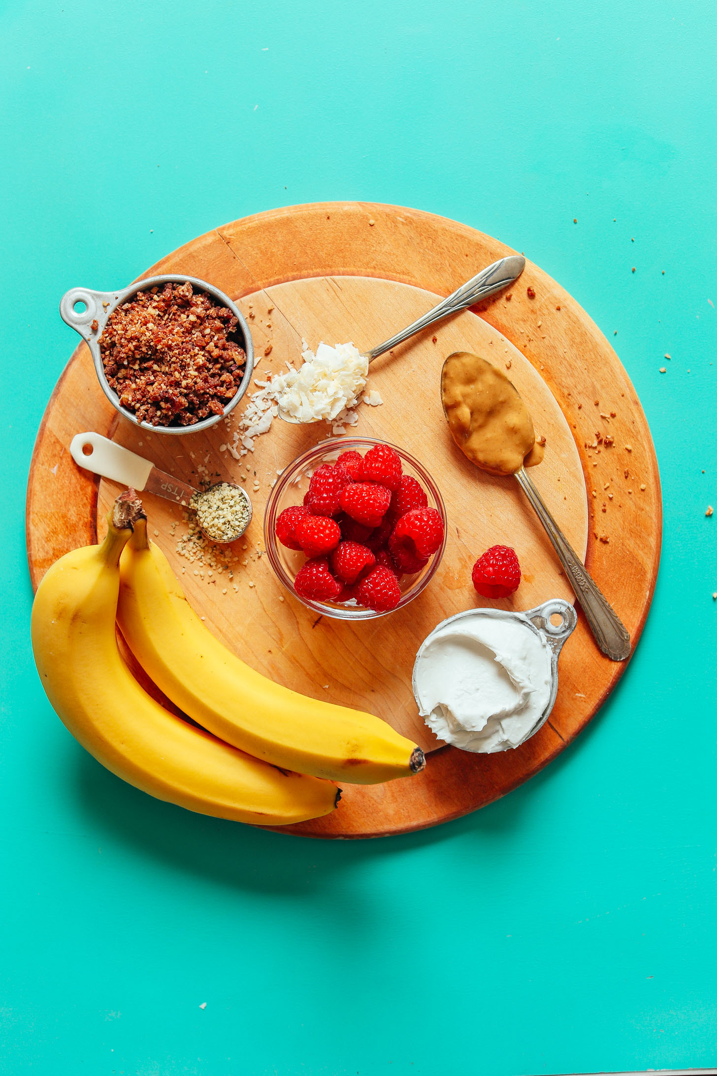 Display of ingredients for Raw Banana Splits including bananas, raspberries, coconut yogurt, flaked coconut, peanut butter, and rawnola