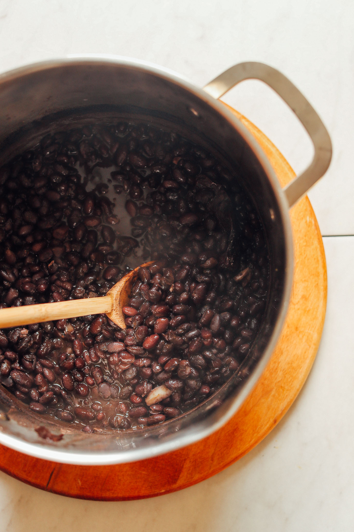 Stirring a large pot of tender, flavorful homemade black beans created using our Easy 1-Pot Black Beans recipe