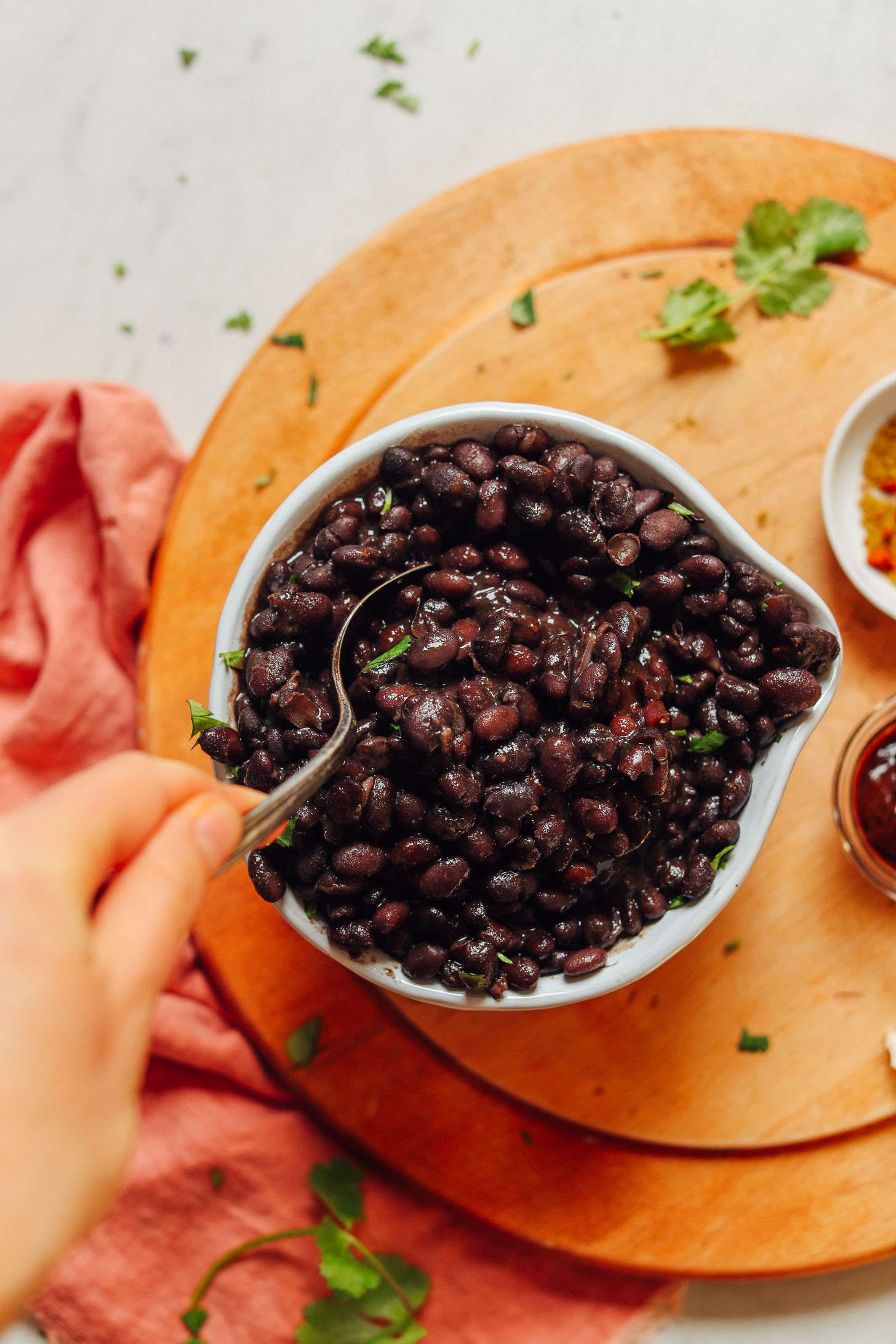 Grabbing a spoonful of homemade black beans that are perfectly tender and flavorful
