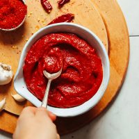 Using a spoon to smooth the top of a bowl of Korean-Inspired homemade Gochujang sauce