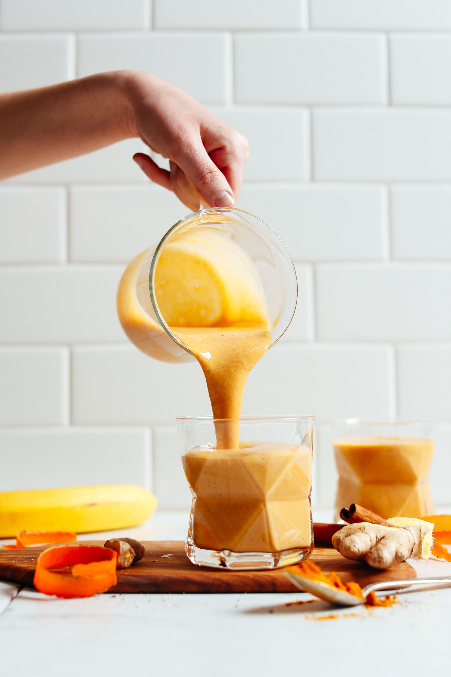 Pouring our vibrantly-colored Vegan Golden Milk Smoothie into a serving glass