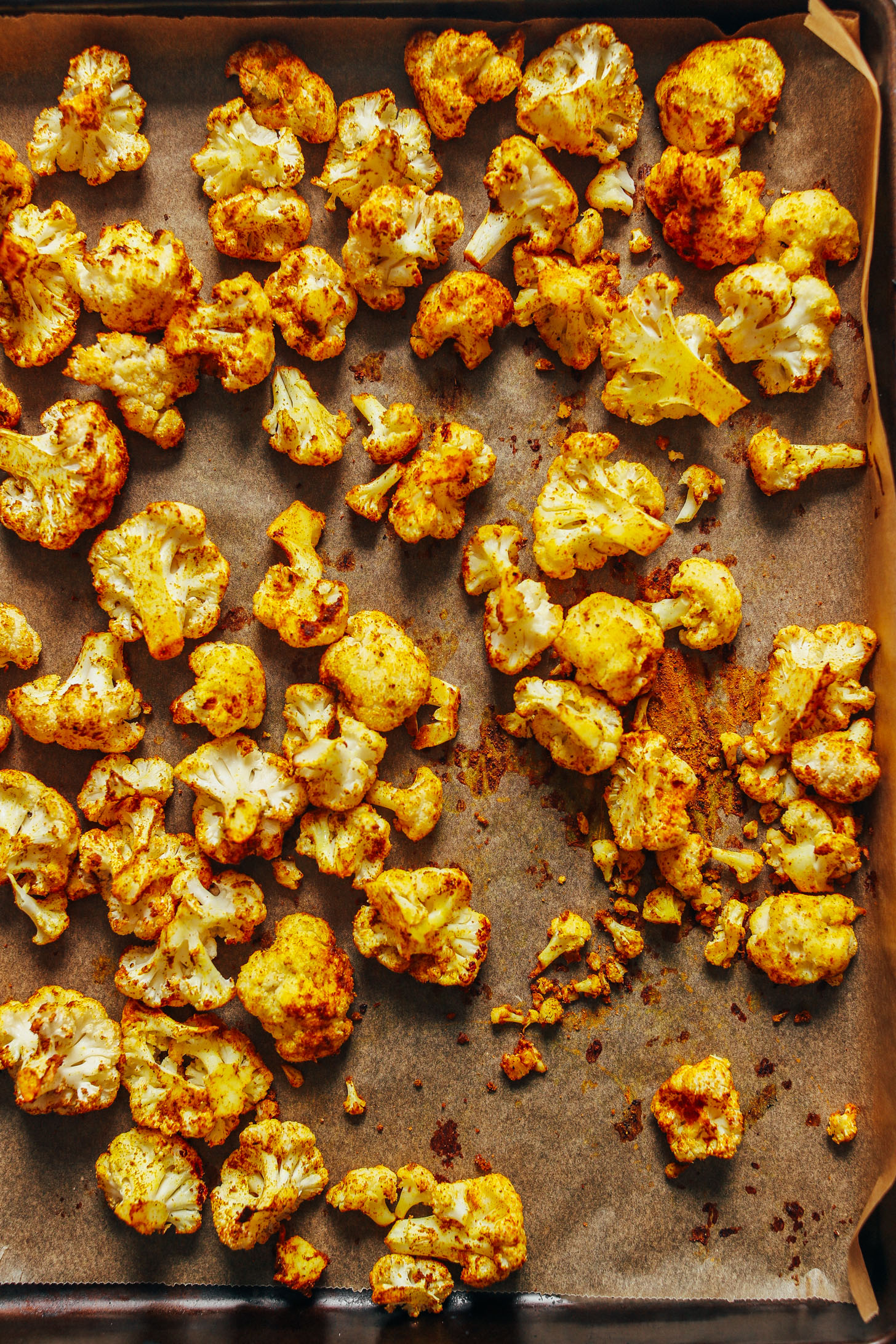 Parchment-lined baking sheet with Curry Roasted Cauliflower fresh from the oven