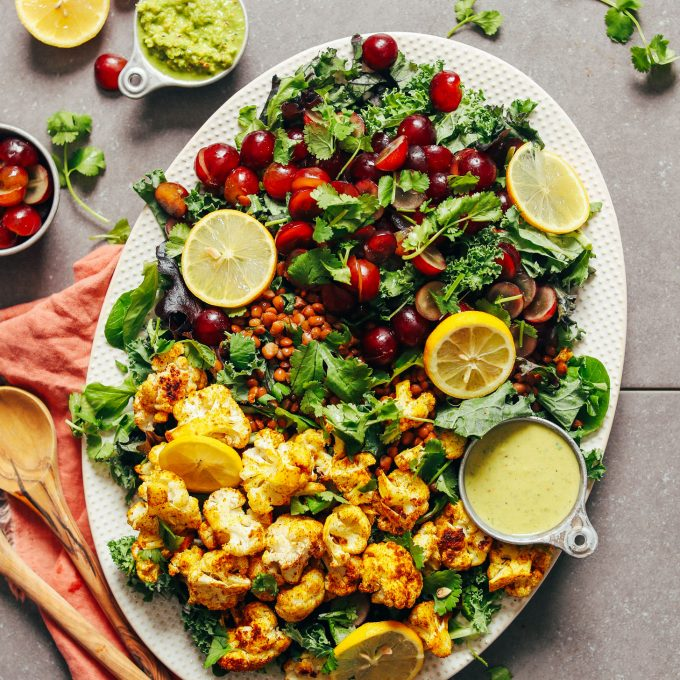 A delicious platter of plant-based and gluten-free Kale Salad with Grapes, Lentils and Curry Roasted Cauliflower
