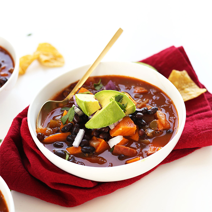 Sliced avocado on a bowl of Black Bean Sweet Potato Chili for our roundup of Plant-Based 1-Pot Dinners