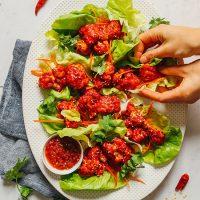 Grabbing some Korean-Inspired Cauliflower Wings wrapped in lettuce leaves with shredded carrot