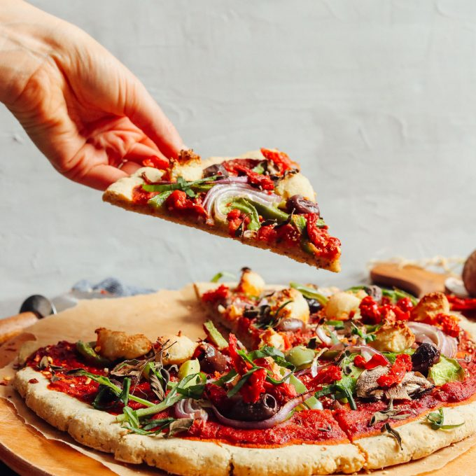 Picking up a slice of gluten-free and vegan pizza made using our Gluten-Free Pizza Crust recipe