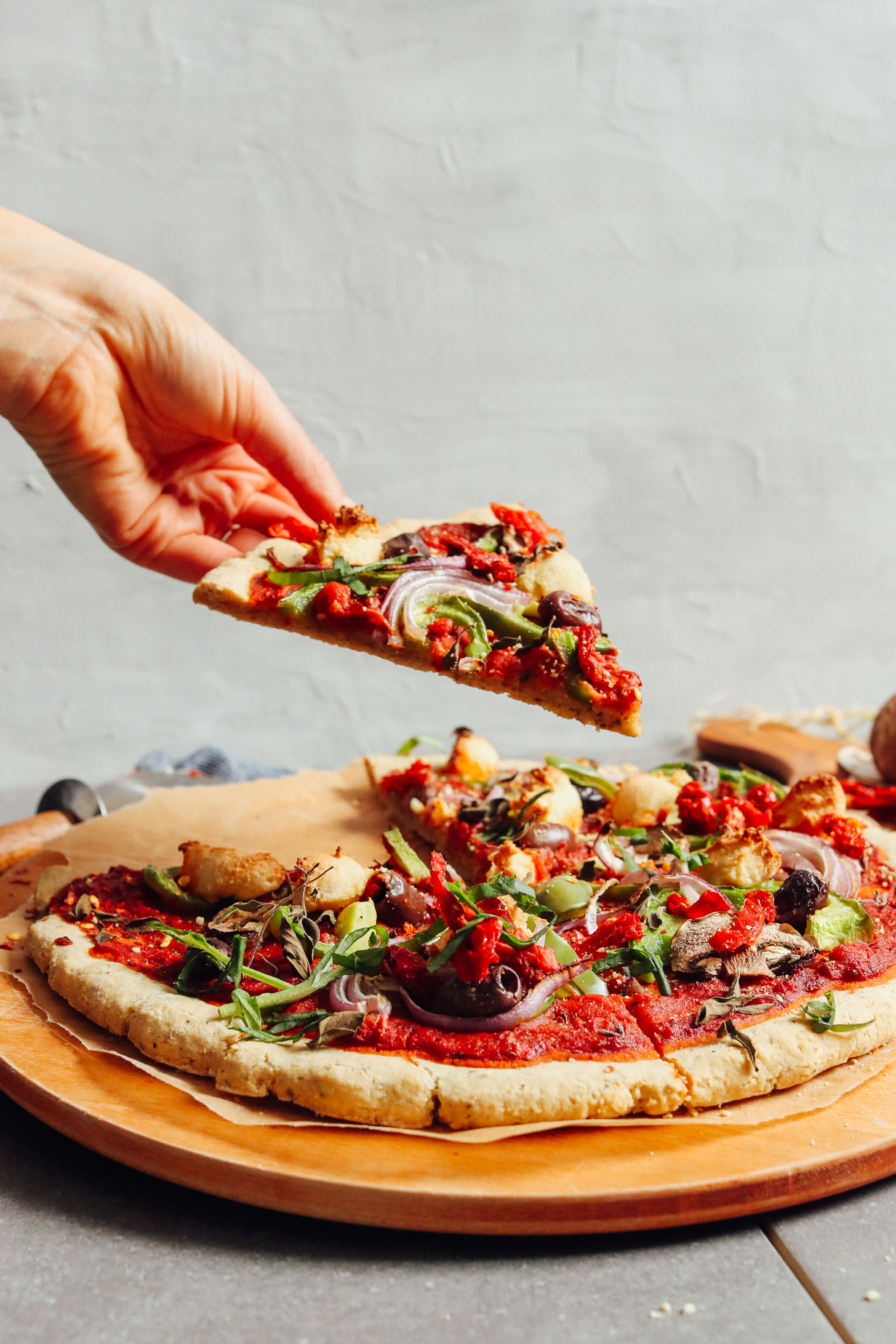 Grabbing a slice of pizza created using our Gluten-Free Pizza Crust recipe