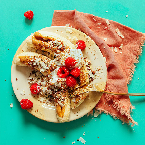 Plate with two Raw Banana Splits topped with nut butter, raspberries, and more