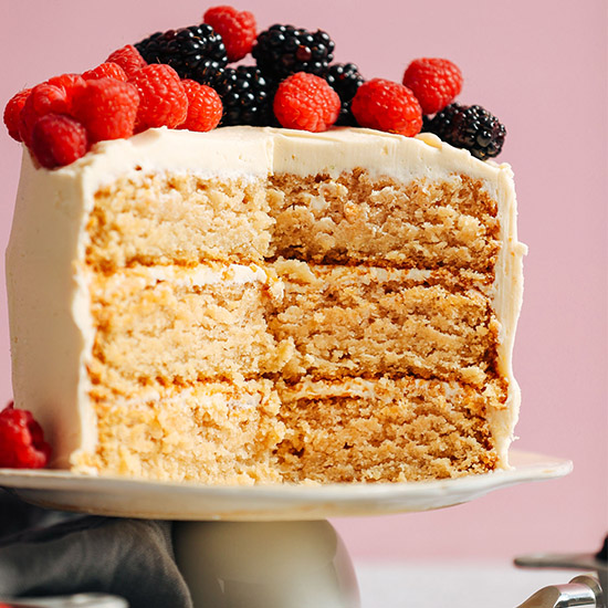Three layer Vegan Gluten-Free Vanilla Cake topped with fresh raspberries and blackberries