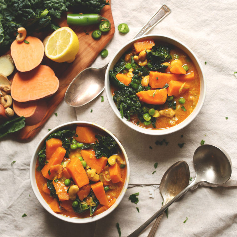 Bowls of our 1-Pot Plant-Based Kale Sweet Potato Curry beside ingredients used to make it
