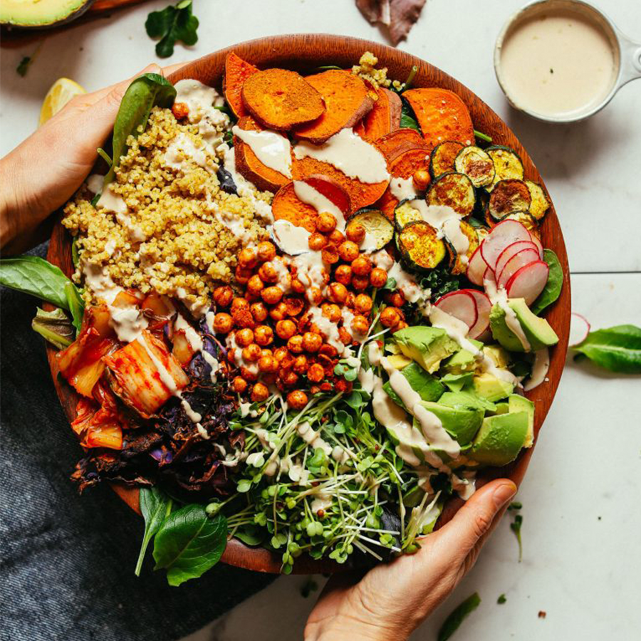 Tahini dressing drizzled over a big wood bowl of our Abundance Green Salad with Savory Tahini Dressing