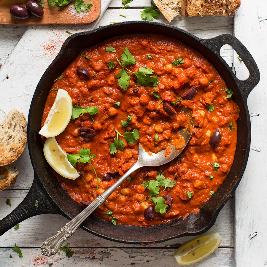 Spoon in a skillet of Chickpea Shakshuka for our roundup of Make Ahead Plant-Based Meals