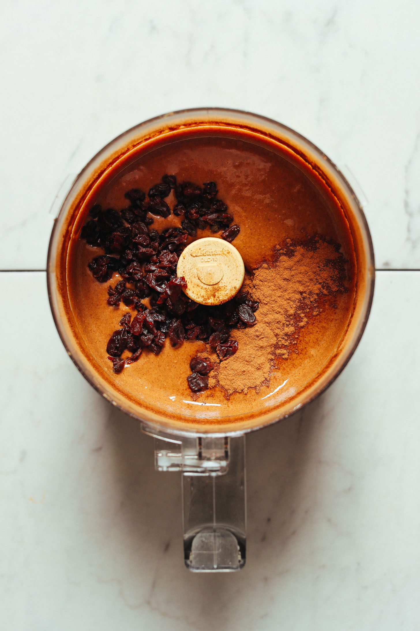 Food processor filled with smooth homemade peanut butter, raisins, and cinnamon