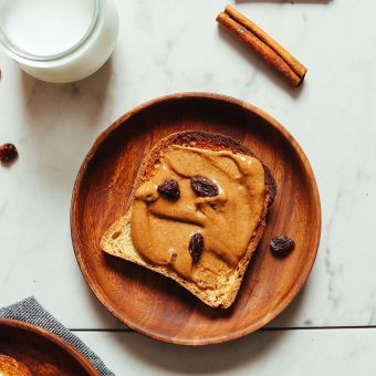 Slice of gluten-free toast smothered with delicious Cinnamon Raisin Peanut Butter for a healthy plant-based breakfast