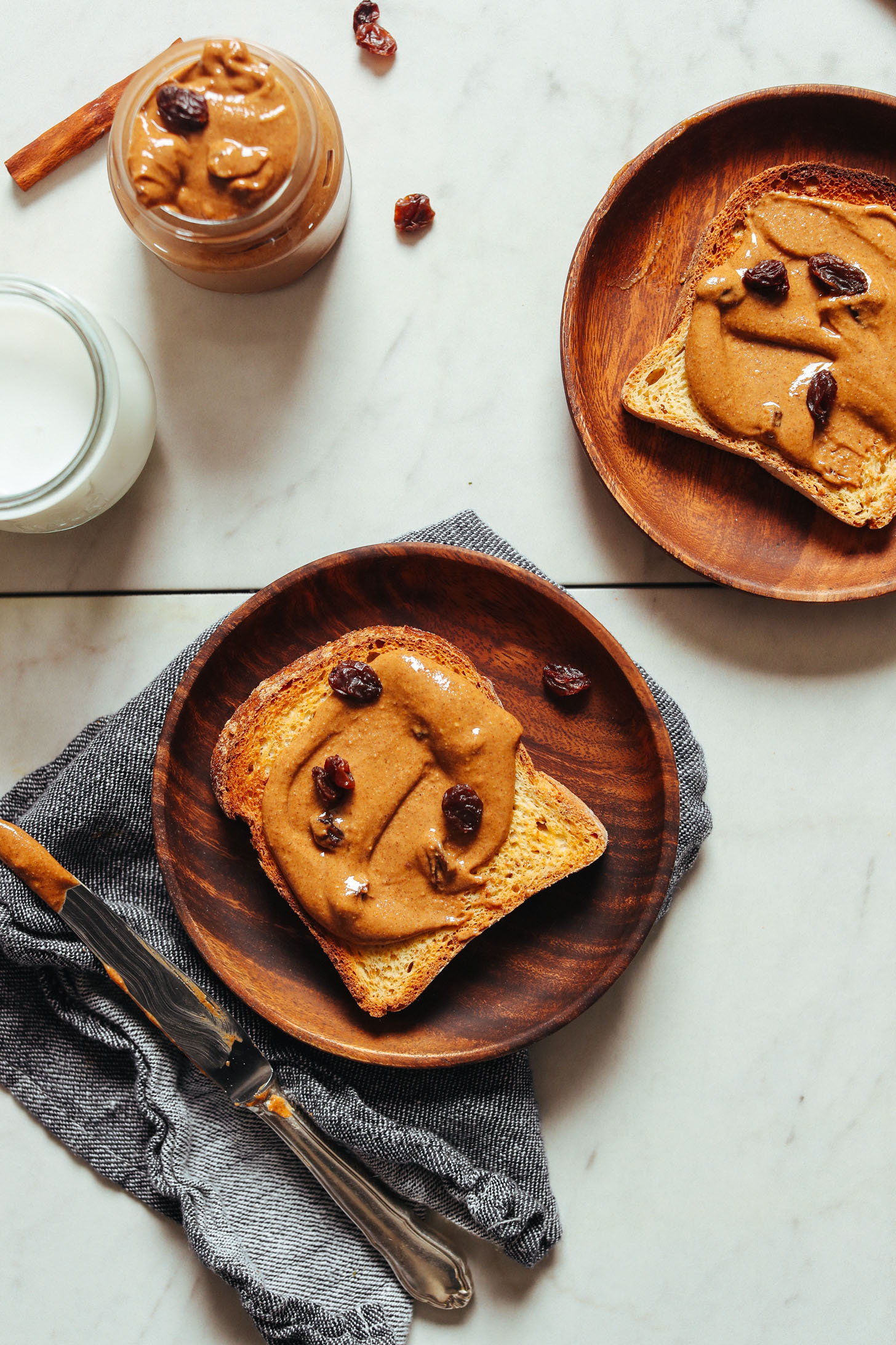 Wood plates featuring slices of gluten-free toast with Cinnamon Raisin Peanut Butter for a delicious plant-based snack