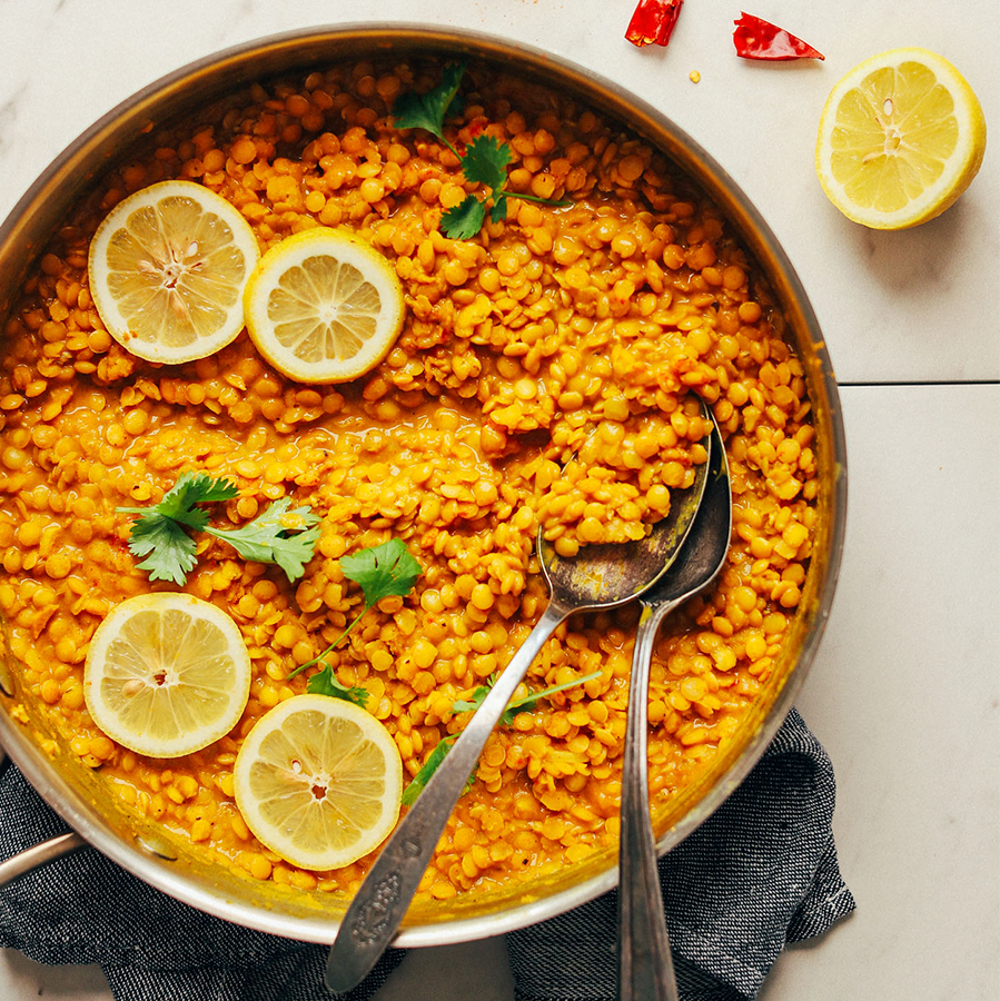 Spoons in a pan of Coconut Curried Golden Lentils for our roundup of 12 Make Ahead Plant-Based Meals