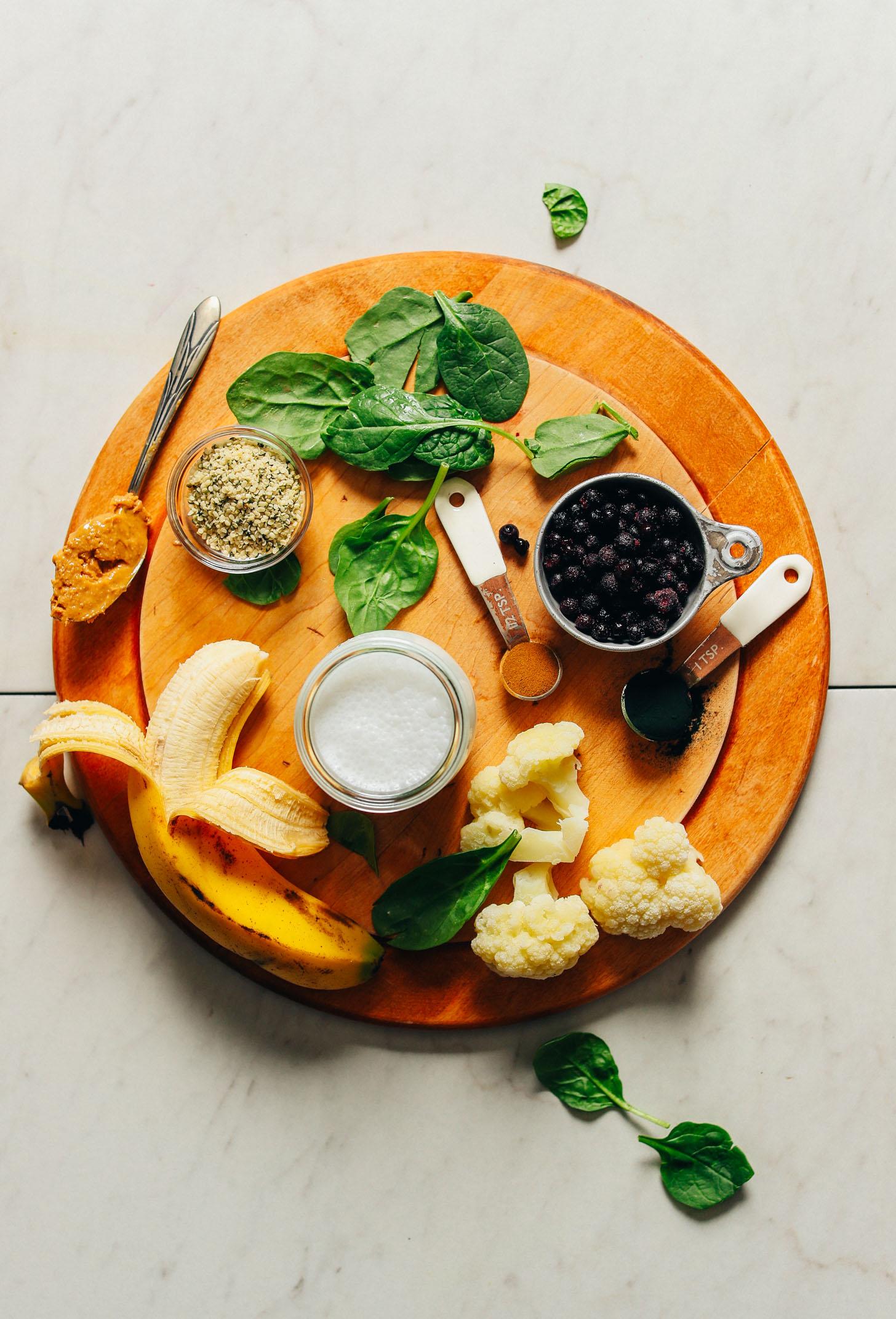 Banana, cauliflower, coconut milk, blueberries, spirulina, cinnamon, spinach, hemp seeds, and peanut butter for making vegan smoothie bowls
