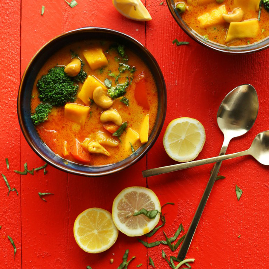 Bowls of Thai Yellow Mango Coconut Curry beside fresh lemons, basil, and spoons