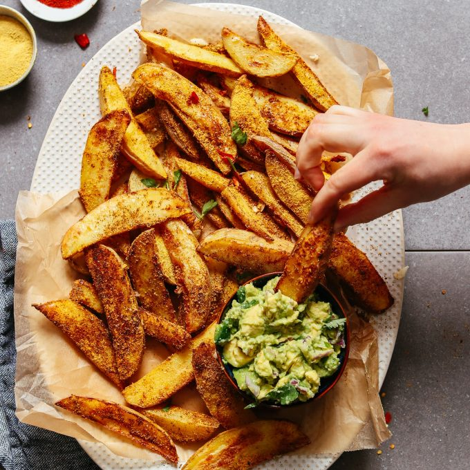 Dipping an oil-free potato fry into guac for a healthy plant-based snack