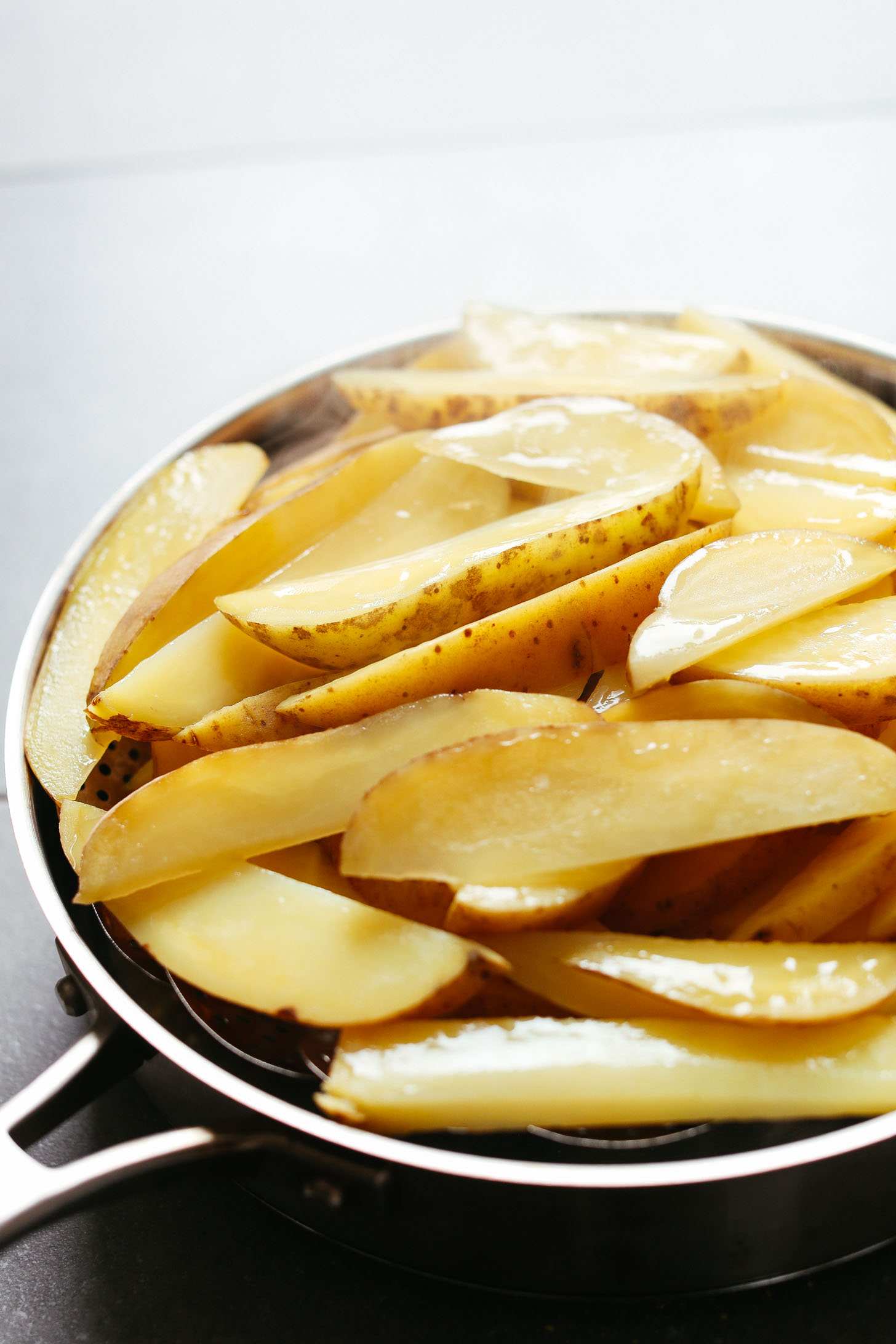 Using a steam basket over a pan to soften potato wedges