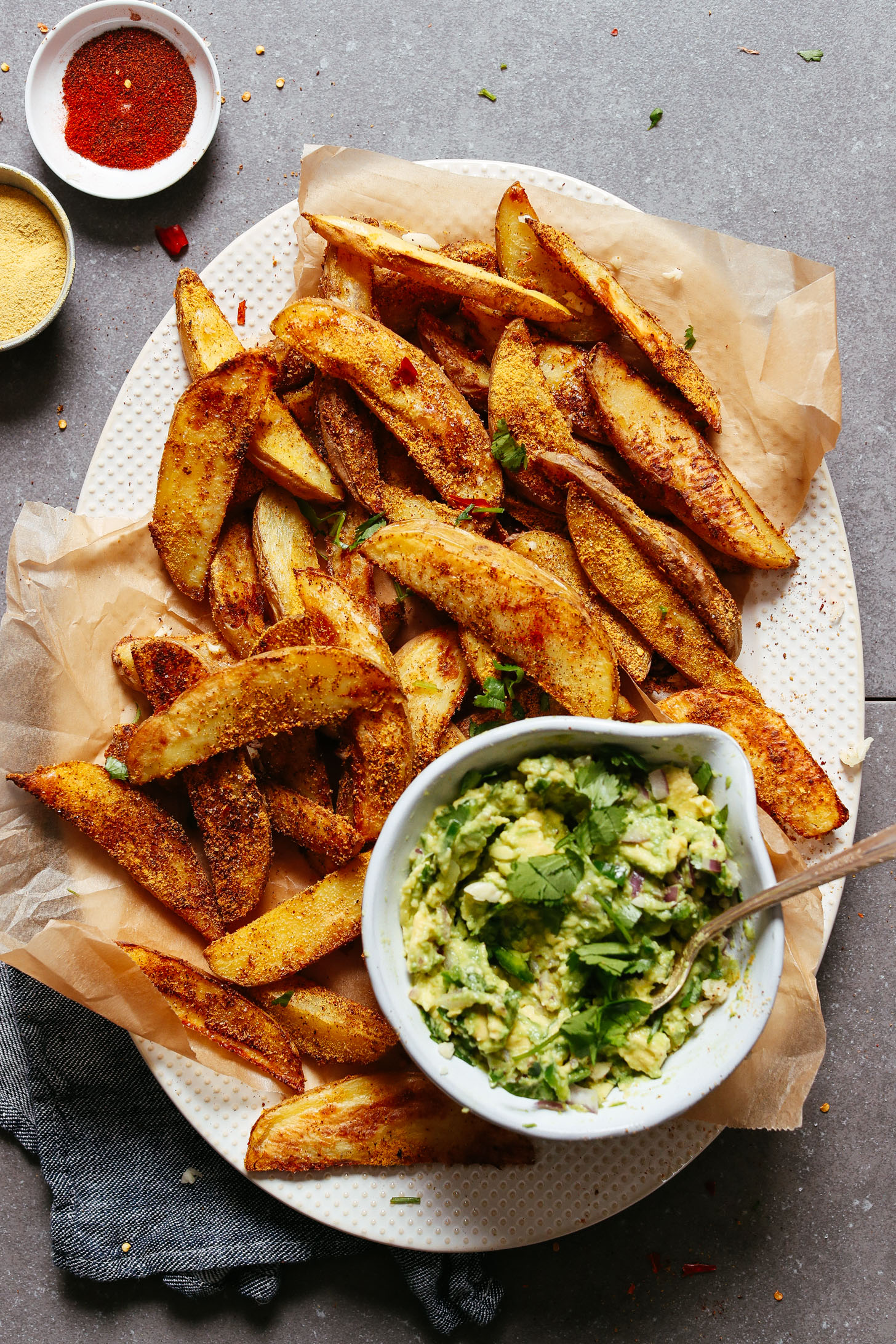 Platter full of Crispy Baked Oil-Free Potato Fries with Cheesy-Chili seasoning and a side of guac