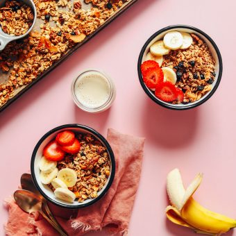 Two bowls of gluten-free homemade granola and dairy-free milk topped with fresh fruit