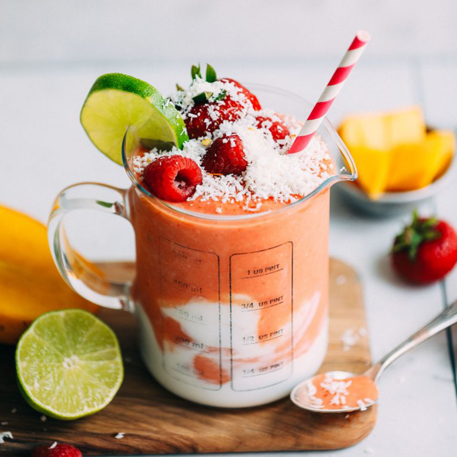 Measuring glass filled with our Mango Berry Smoothie for a Spring-Inspired Recipe