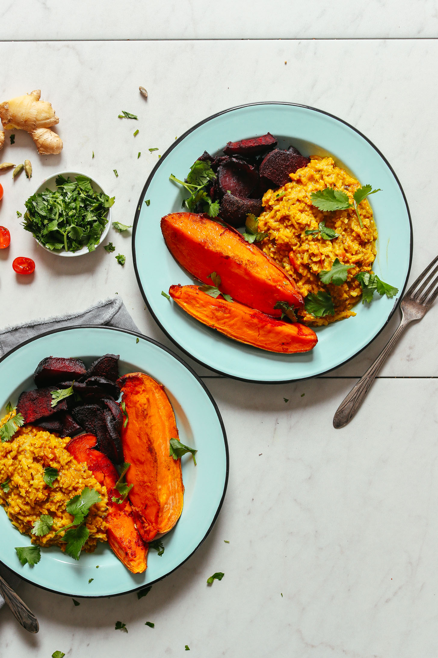 Two plates filled with roasted sweet potato and beets alongside Cauliflower Rice Kitchari for a comforting plant-based meal