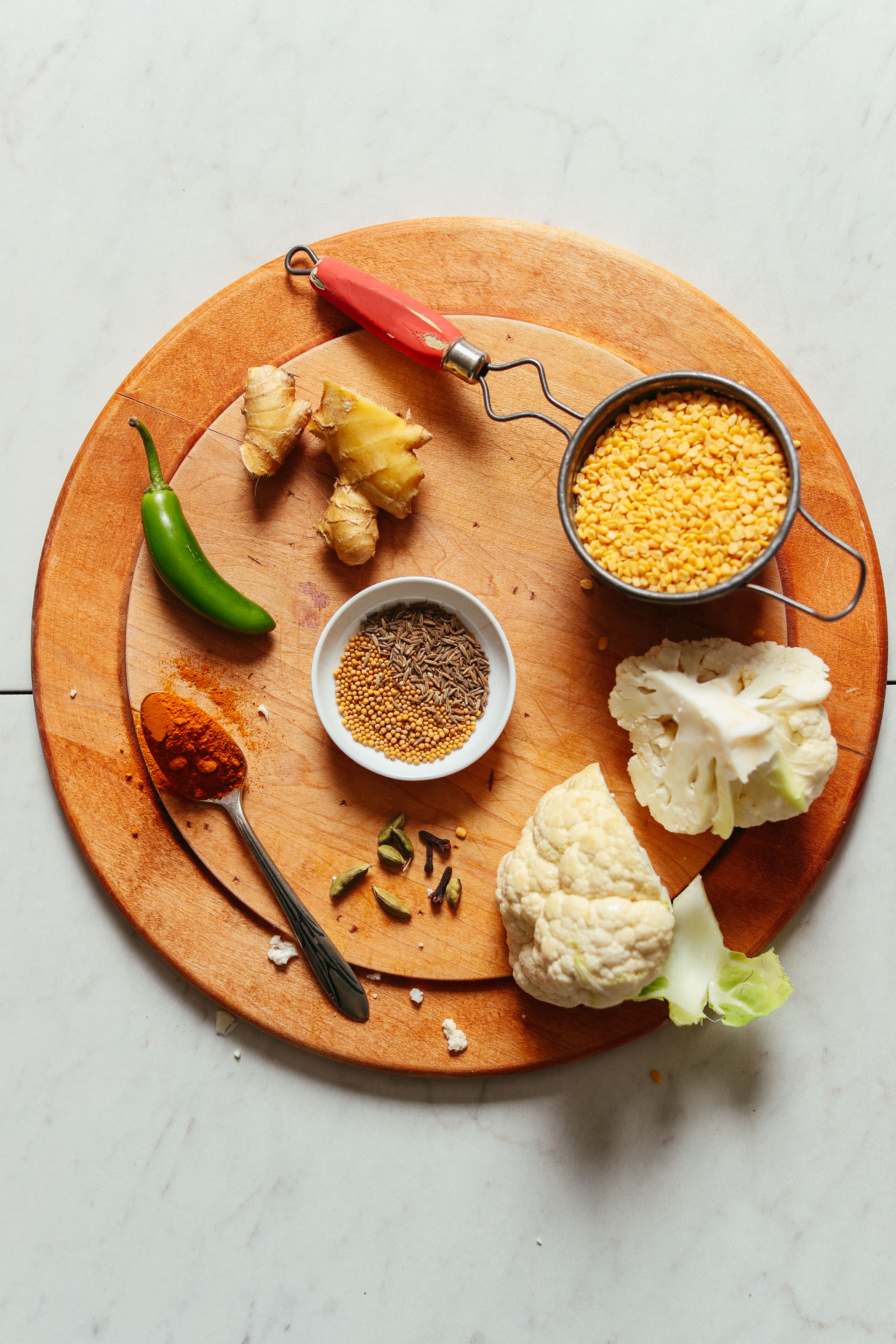 Wood cutting board showcasing ginger, serrano, cauliflower, and moong dal for making Cauliflower Rice Kitchari