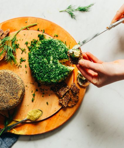 Using a knife to spread homemade vegan cheese onto a cracker for a plant-based snack
