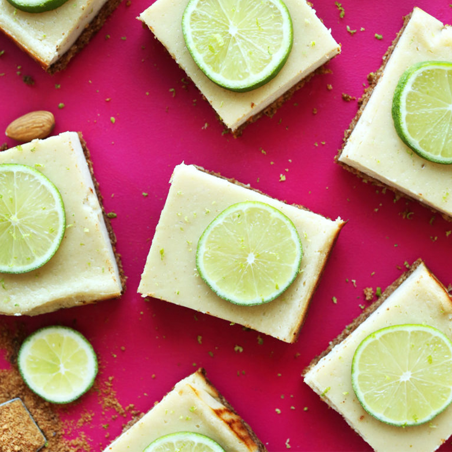 Key lime pie bars on a bright pink background for our roundup of Spring-Inspired Recipes