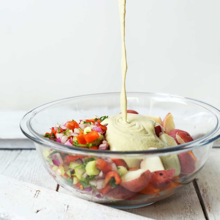Pouring dressing onto a bowl of Vegan Potato Salad for our Spring-Inspired Recipes roundup