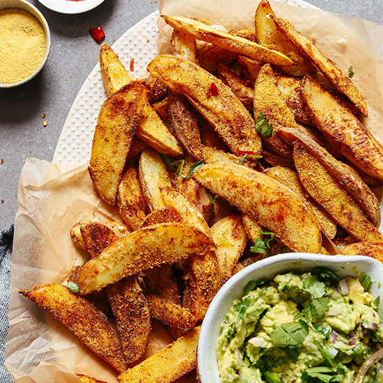 Parchment-lined platter filled with Oil-Free Baked Cheesy Fries and a bowl of guacamole