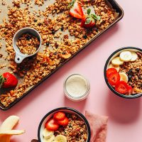 Bowls and baking sheet of homemade Vegan Oil-Free Granola topped with fresh fruit
