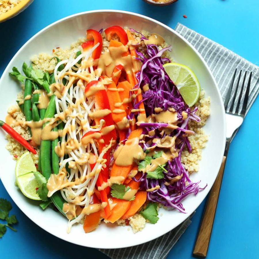Big bowl of Quinoa Gado Gado topped with peanut sauce for our Spring-Inspired Recipes roundup
