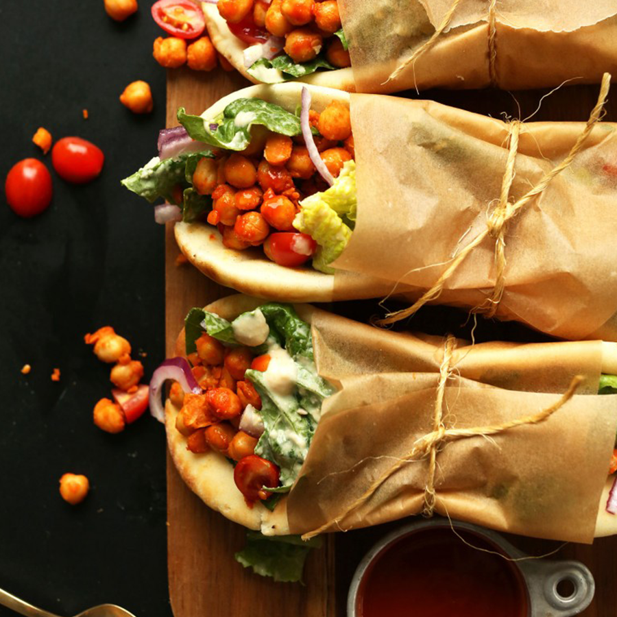 Cutting board with three Buffalo Chickpea Wraps for our Plant-Based Lunch Recipes roundup
