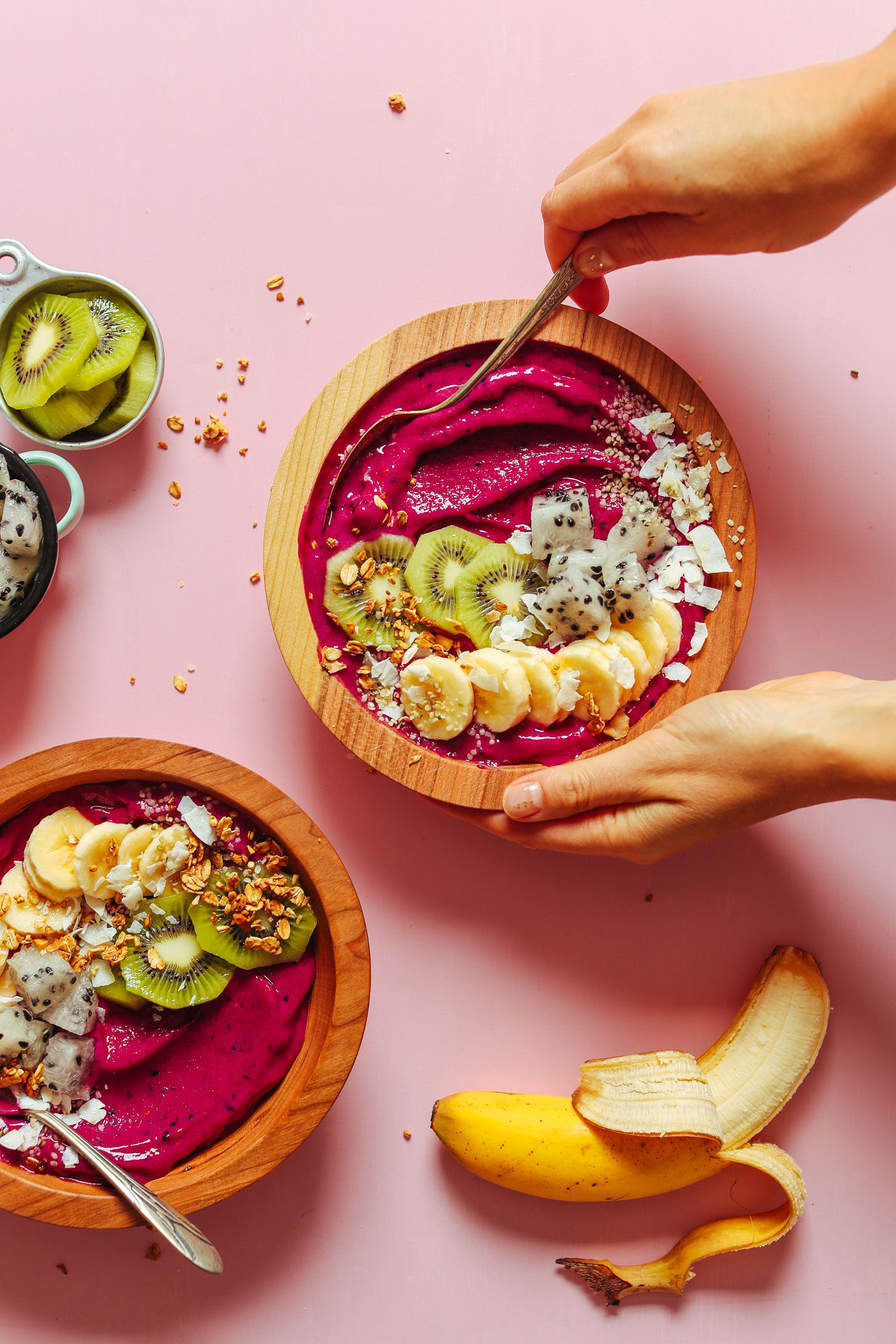 Grabbing a spoonful of our vegan Dragon Fruit Smoothie Bowl topped with fresh fruit, coconut, and granola