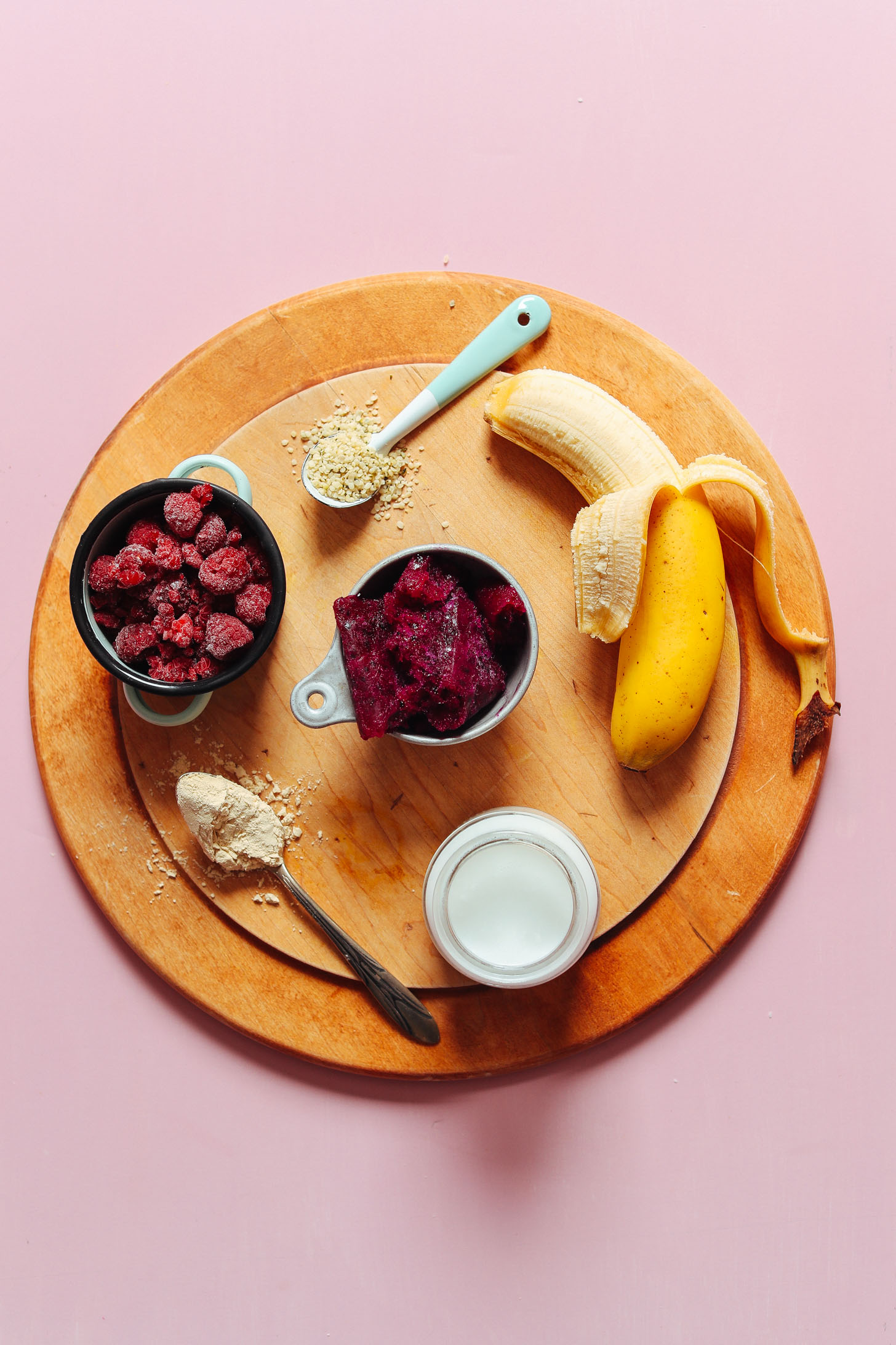 Wood cutting board with banana, hemp seeds, frozen raspberries, dragonfruit, vegan protein powder, and coconut milk for making a Dragon Fruit Smoothie Bowl