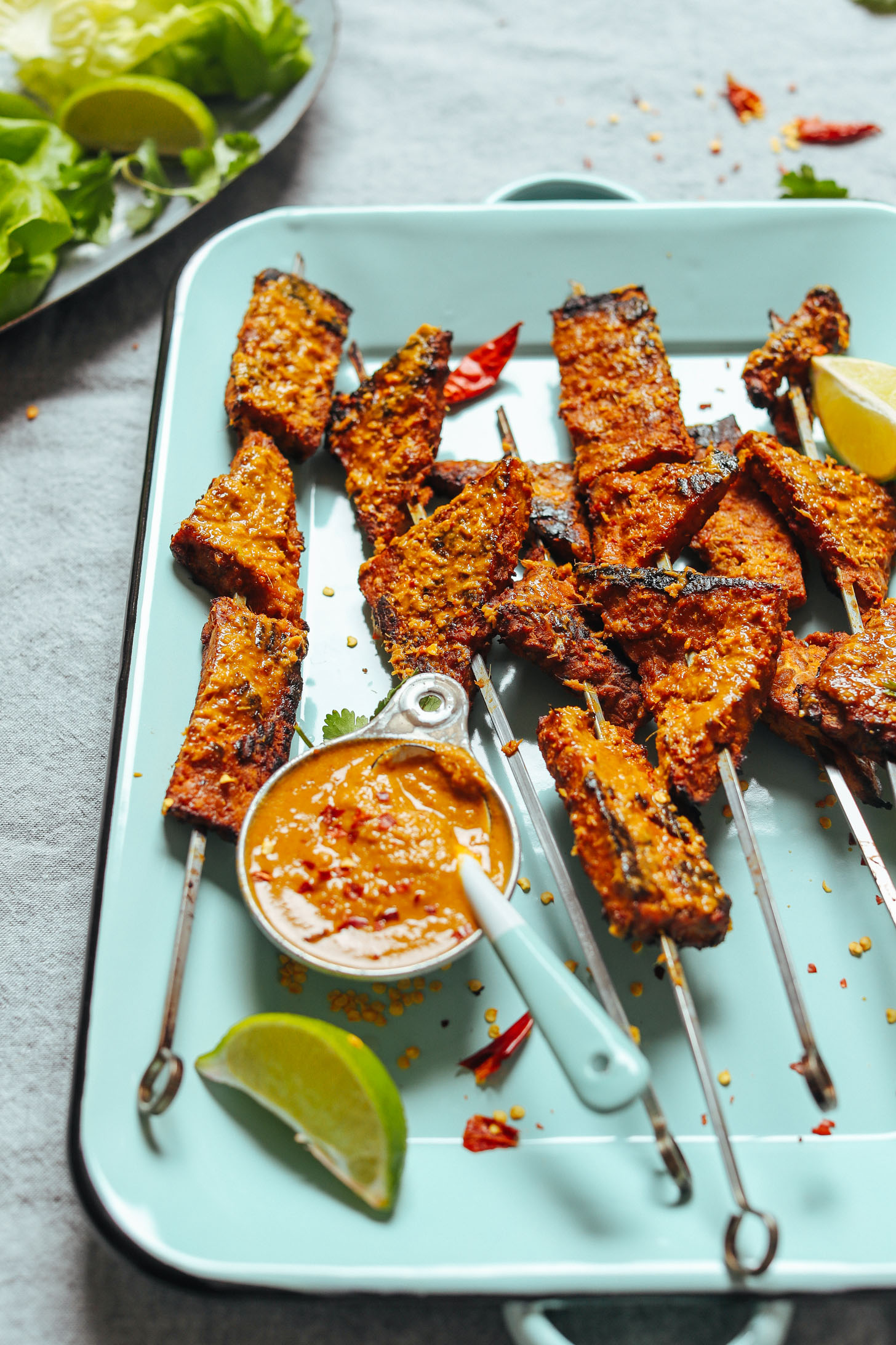 Blue platter with grilled vegan tempeh skewers and lemongrass sauce