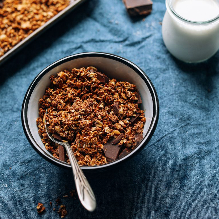 Bowl of Dark Chocolate Sea Salt Granola beside a glass of almond milk for our roundup of Vegan Breakfast Recipes