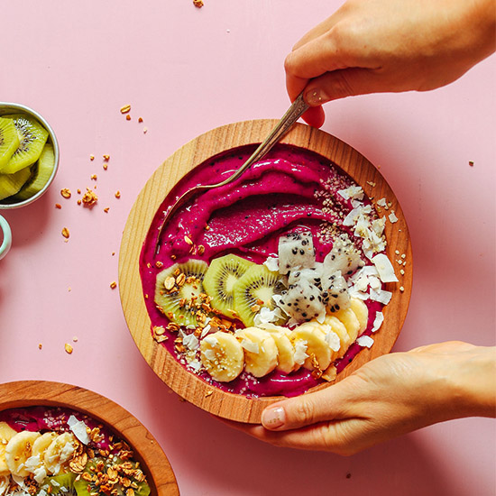Using a spoon to scoop up a bite of a delicious Dragon Fruit Smoothie Bowl topped with fresh fruit